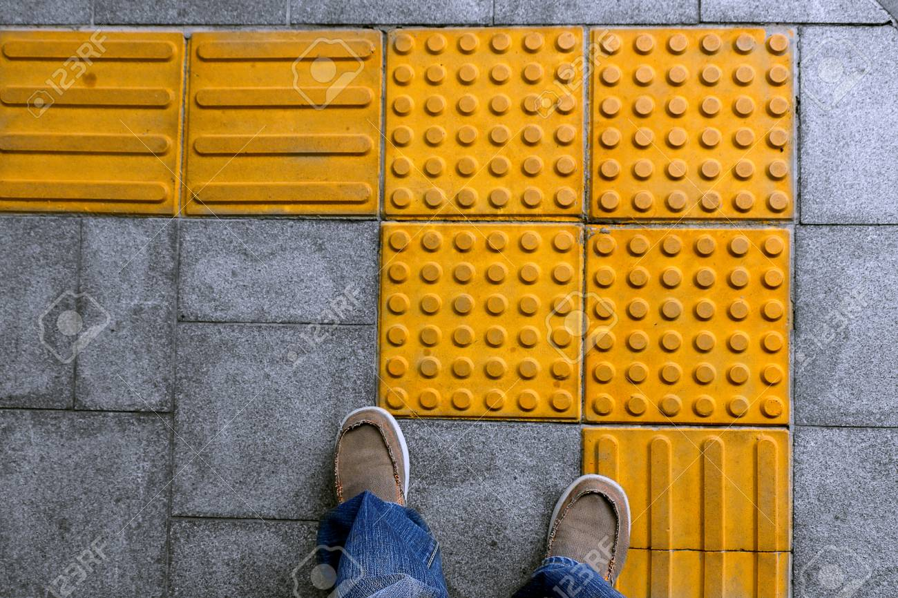 Shoes on block tactile paving for blind handicap on tiles pathway shoes on block tactile paving for blind handicap on tiles pathway walkway for blindness people dailygadgetfo Choice Image