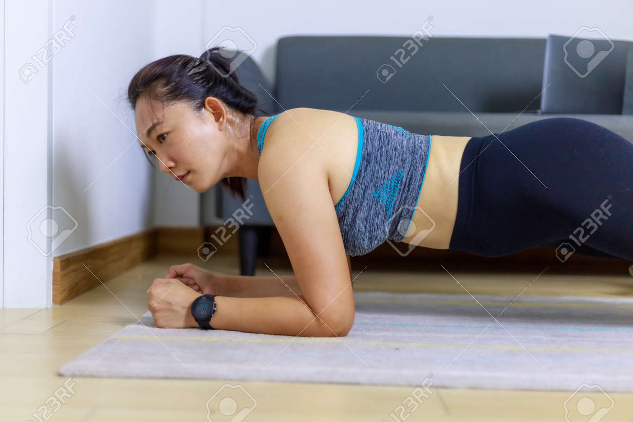 Portrait beautiful adult (40 years old) Asian woman doing Home Workout in Sports Clothing with Stretching Exercise in the room white background. People's body and health care lifestyle concepts. - 166105550
