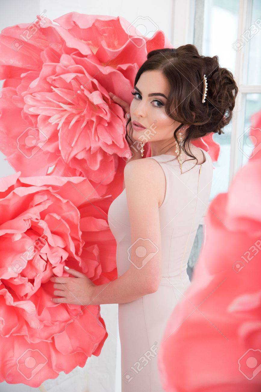 Beautiful sexy girl in a long dress with a huge pink flowers stock beautiful sexy girl in a long dress with a huge pink flowers sitting by the window mightylinksfo