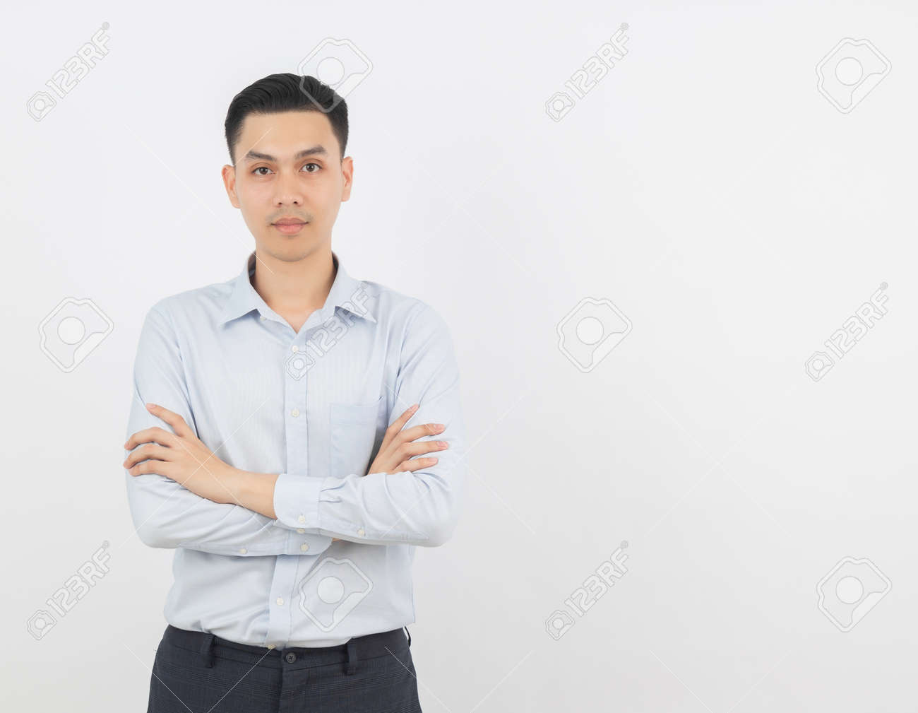 Young handsome asian business man looking to camera with arms crossed isolated on white background. - 145582580