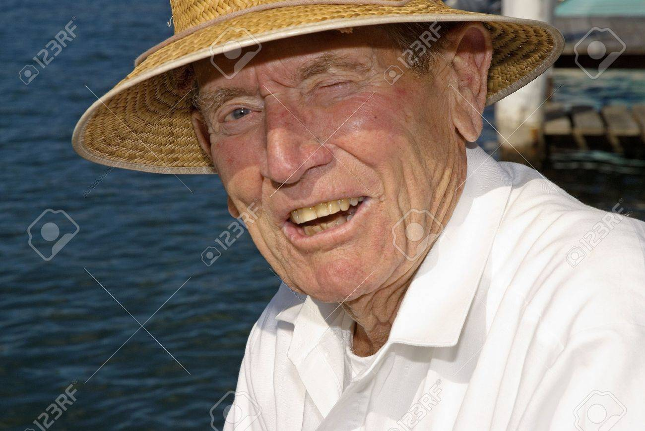 Elderly man with sun hat at waters edge - 9385779
