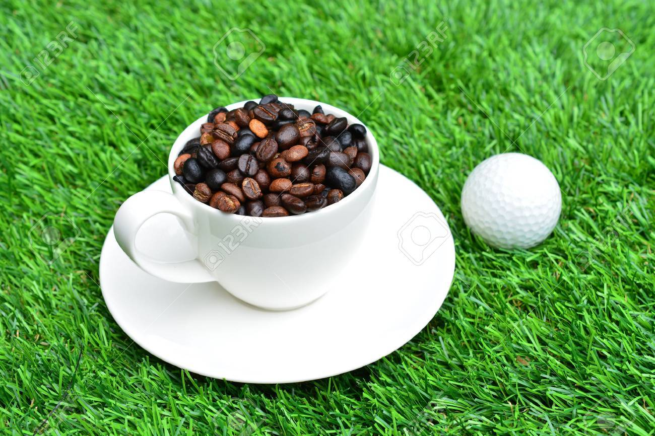 Cup of coffee and golf on green grass - 33009273