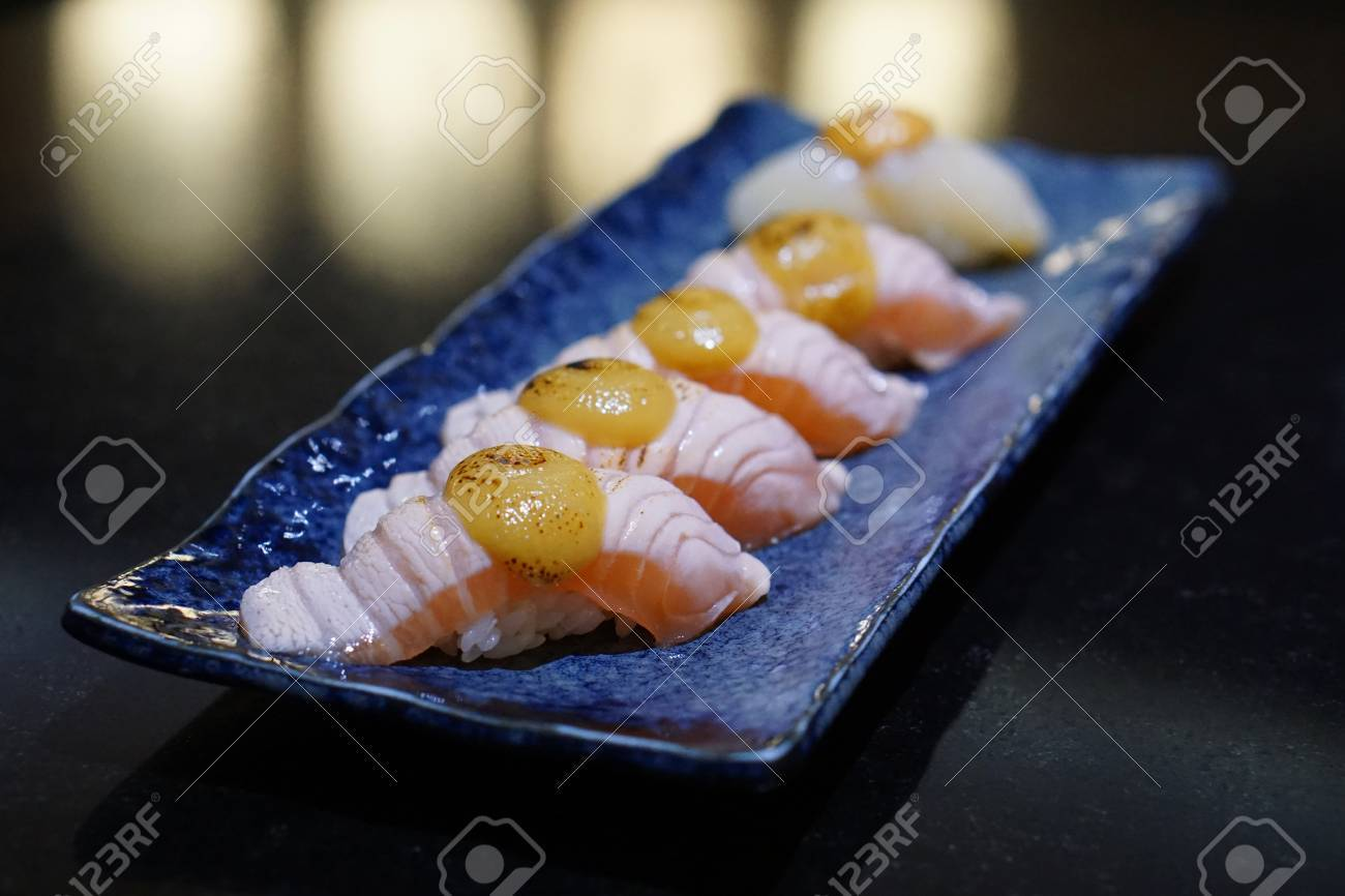 Blue Fish Sushi | Closeup Of Salmon Aburi Sushi Topped With Saikyo Sauce On A Blue