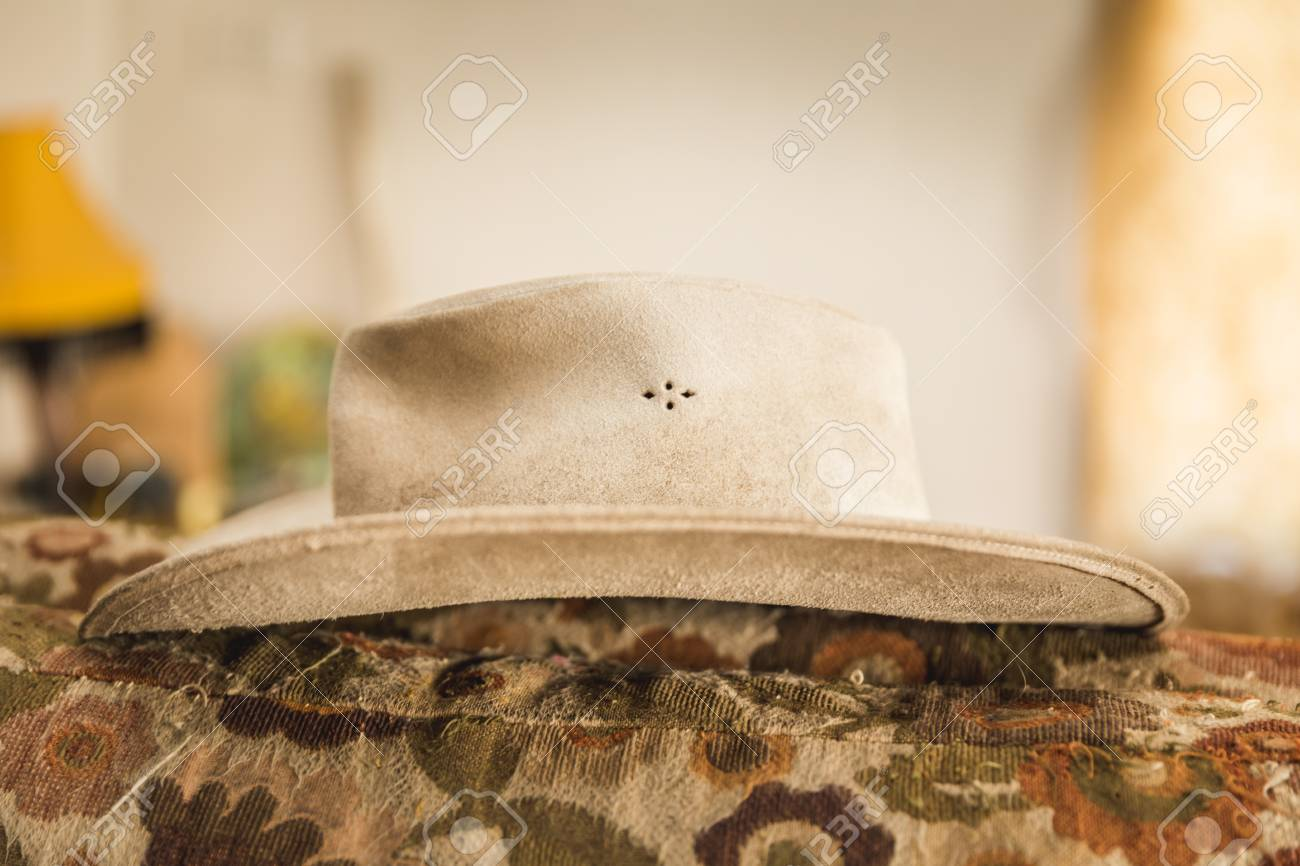 7e87ce42031e0 Leather cowboy hat resting on an old couch. Stock Photo - 77190264