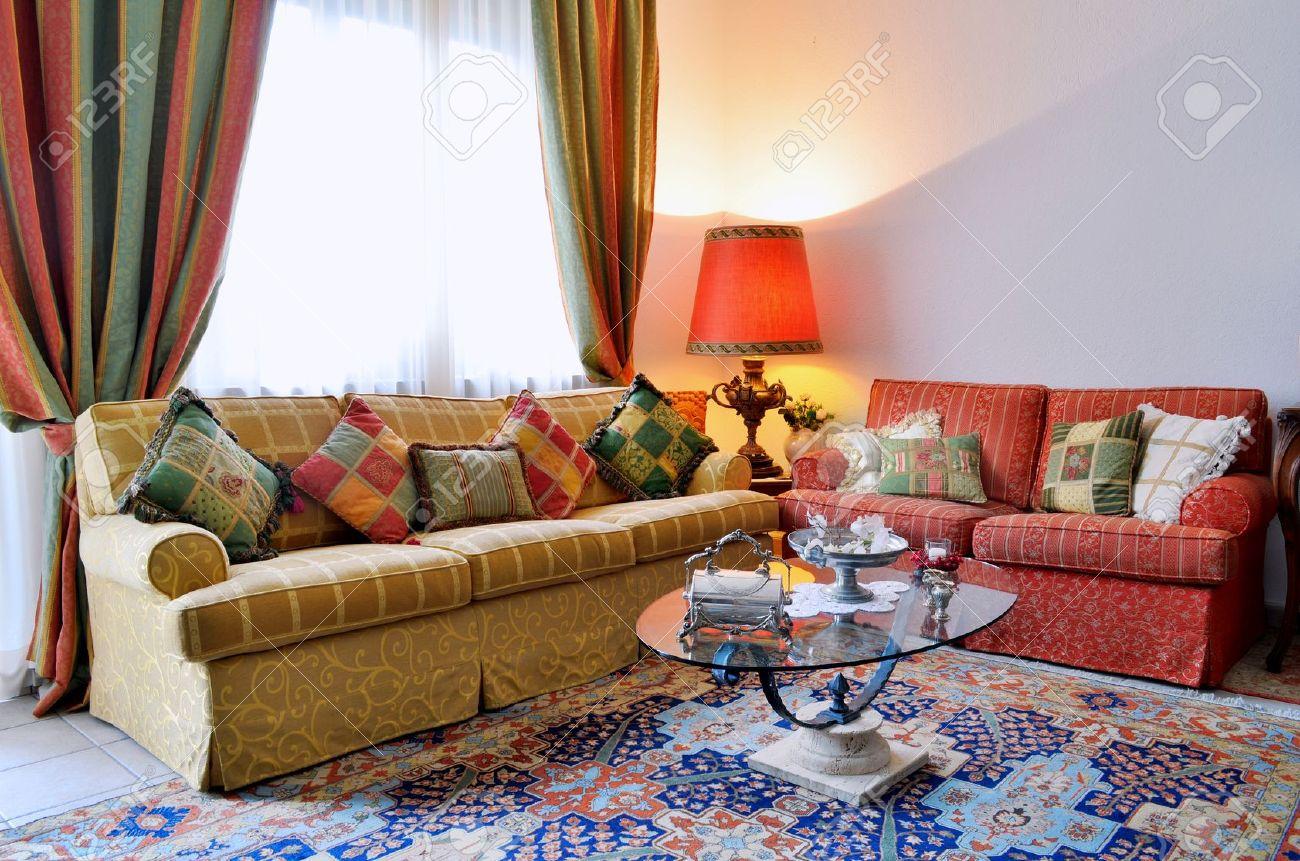 Elegante woonkamer met klassiek ogende sofa, kleurrijke gordijnen ...