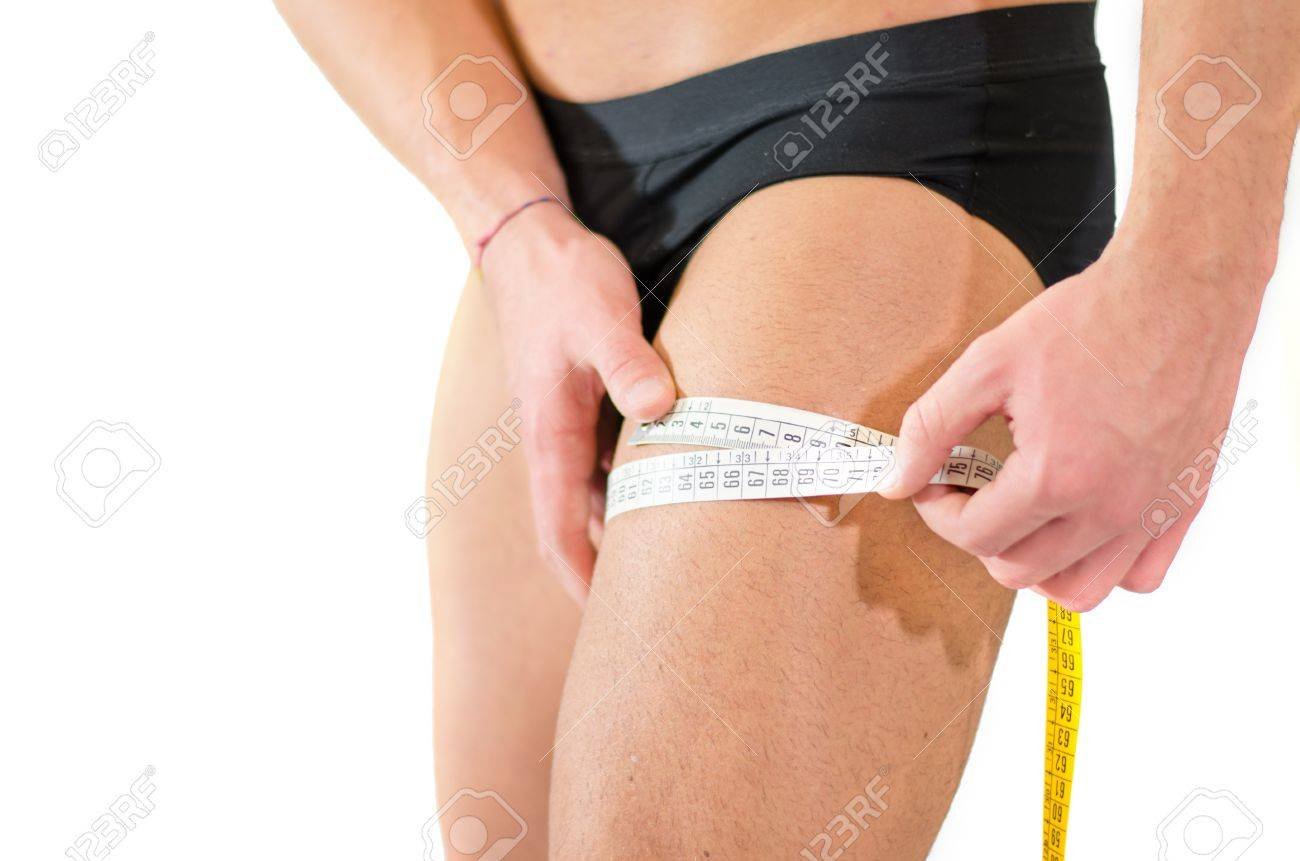 Close-up of young man measuring size of his thigh muscles with tape meter Stock Photo - 18811612