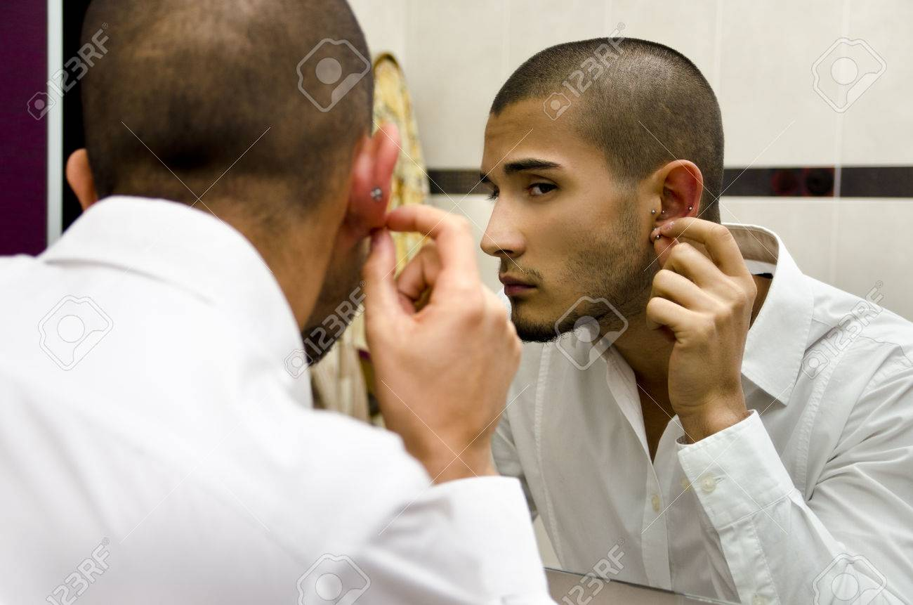 Handsome Young Man Touching And Examining His Ear Piercings Stock Photo   24673980
