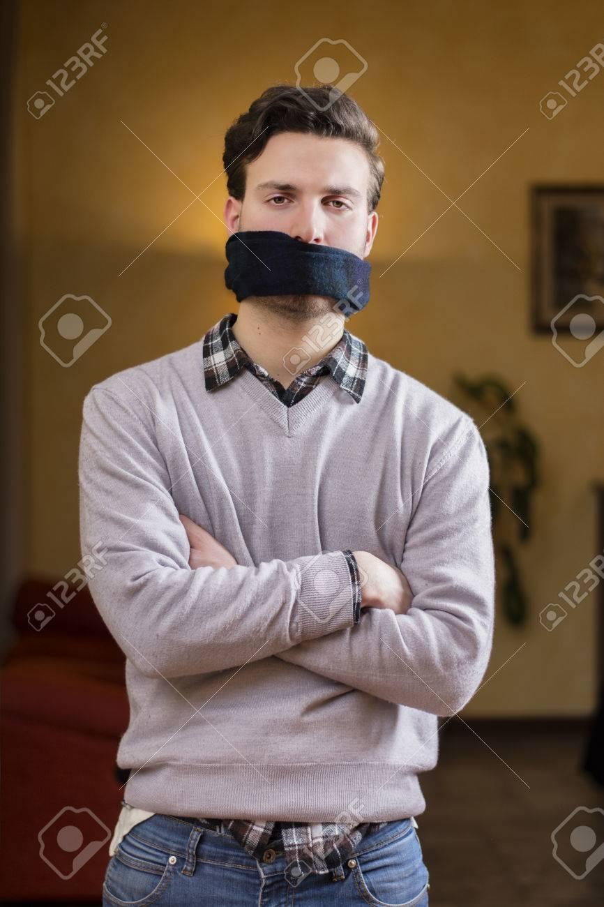 descuento de venta caliente fábrica zapatillas de deporte para baratas Hombre joven con la mordaza (pañuelo) en la boca no puede hablar