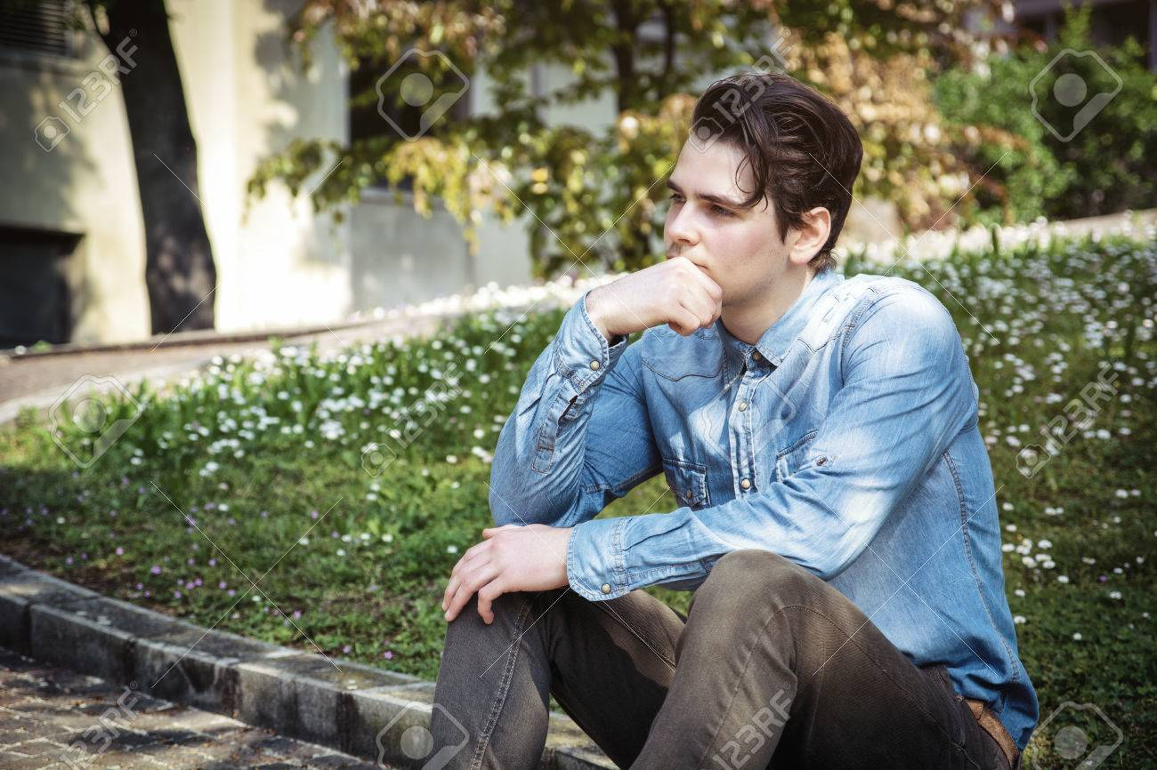 Vivre avec la nostalgie du passé : Bon ou mauvais ? 28333043-young-man-sitting-outdoors-in-public-park-with-hand-on-his-chin-looking-away-thinking