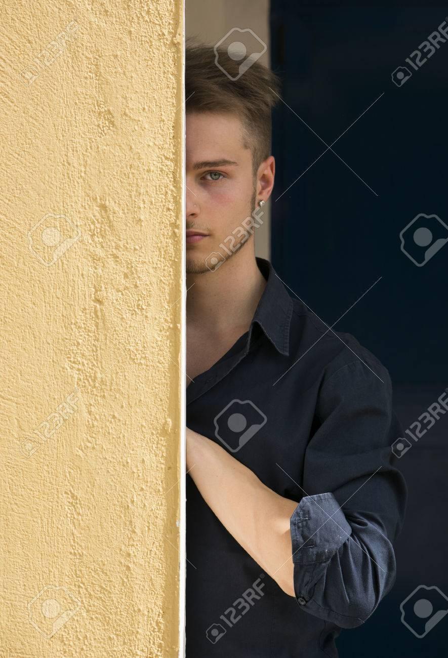 aedd3d92446b80 Knappe blonde jonge man ondergedoken helft gezicht achter de muur op zoek  naar camera met één