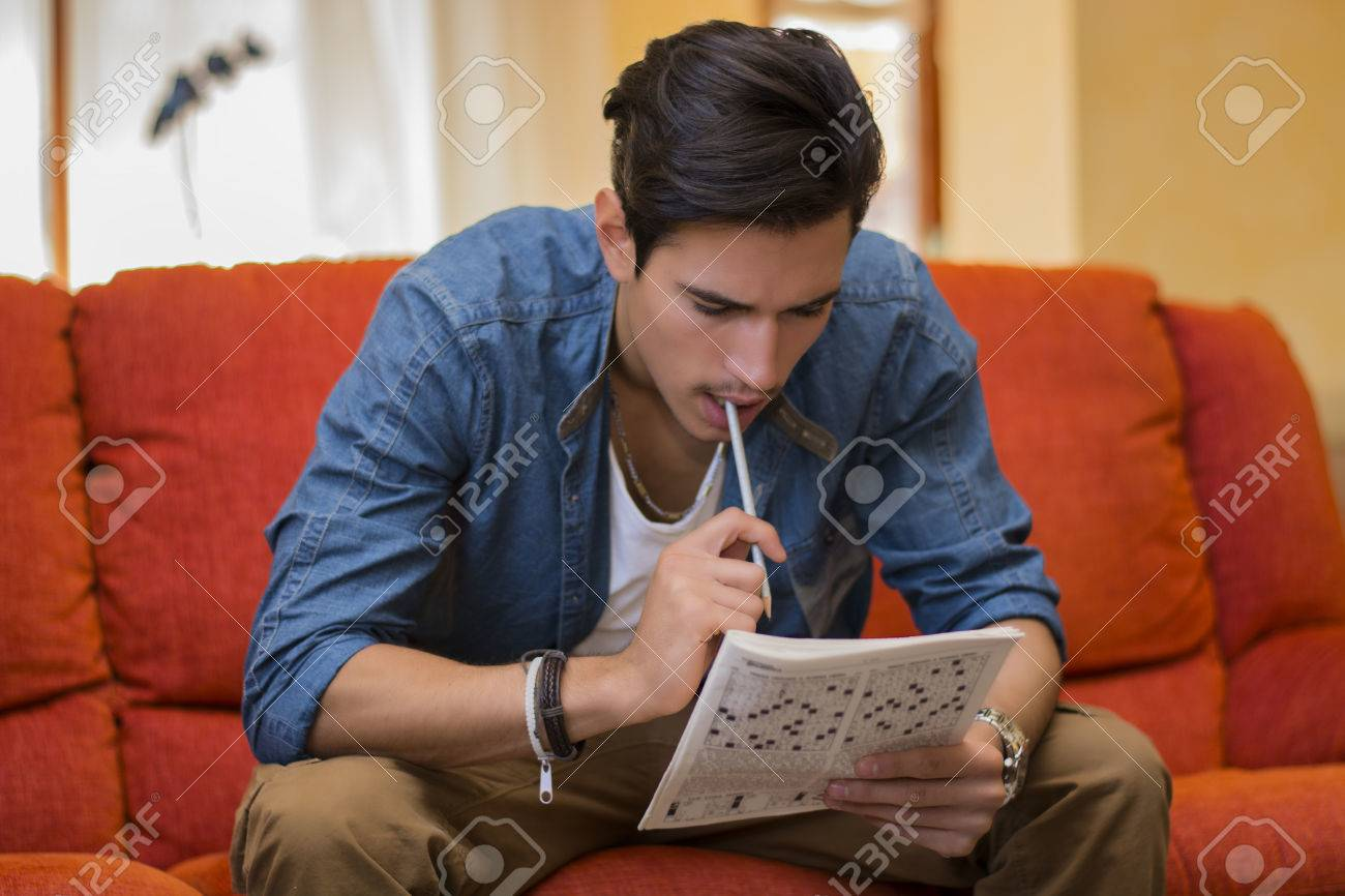 Young Man Sitting Doing A Crossword Puzzle Looking Thoughtfully Stock Photo Picture And Royalty Free Image Image 32269770