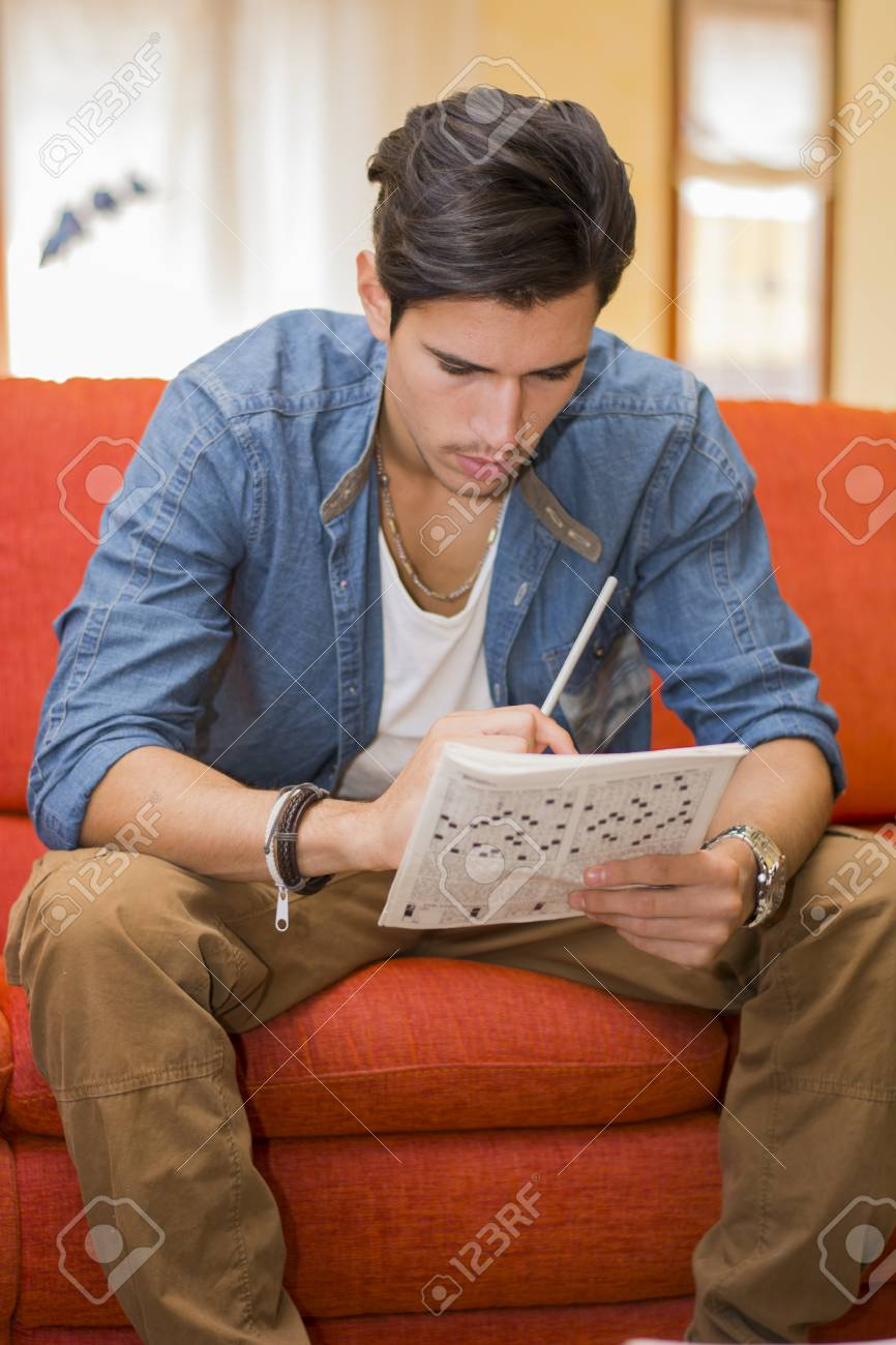 Young Man Sitting Doing A Crossword Puzzle Looking Thoughtfully Stock Photo Picture And Royalty Free Image Image 32269655