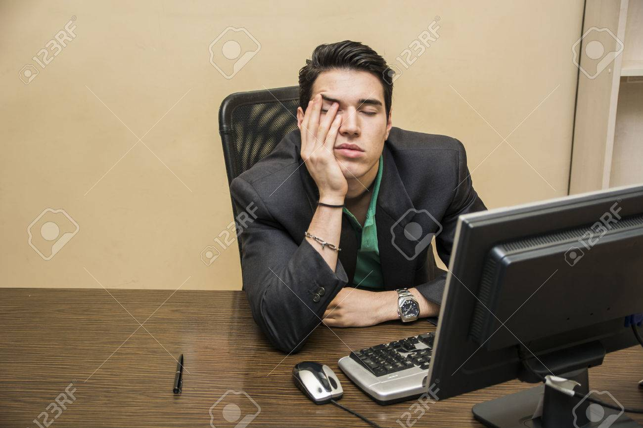 tired bored young businessman sitting at his desk in front of