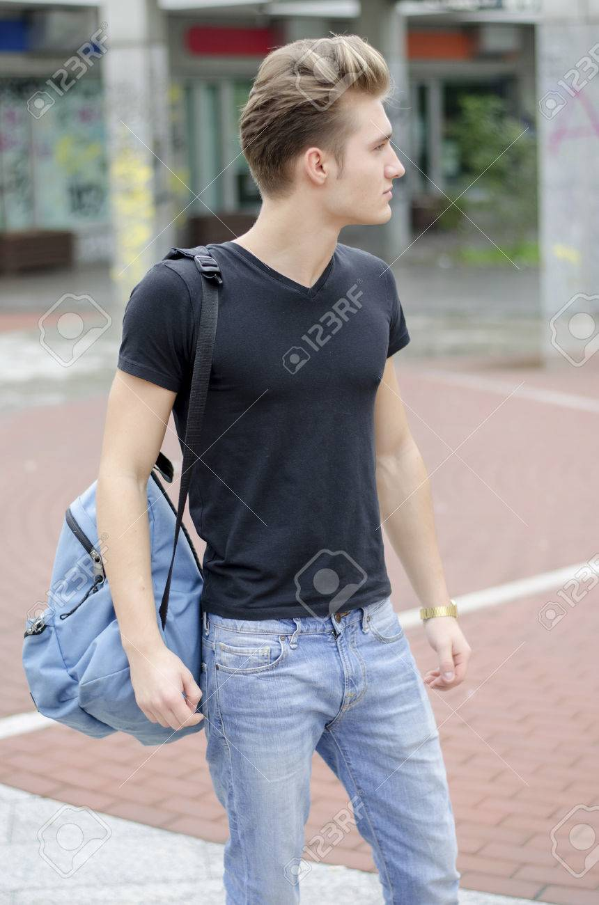 Black t shirt and jeans - Attractive Young Man Wearing Black T Shirt And Jeans With Back Pack Standing Outside Stock