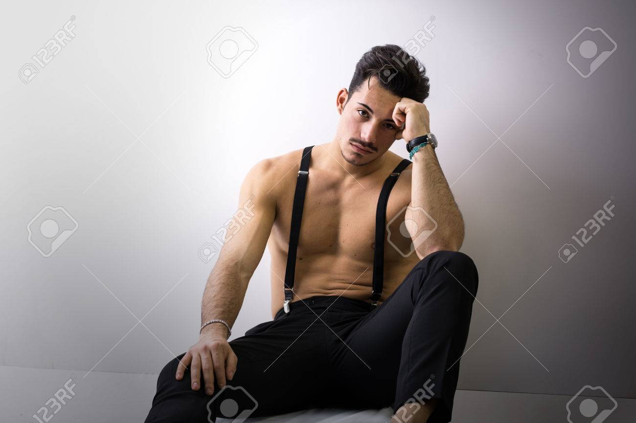 mieux aimé garantie de haute qualité En liquidation Torse nu jeune homme athlétique avec bretelles et pantalon noir assis sur  le plancher, regardant la caméra