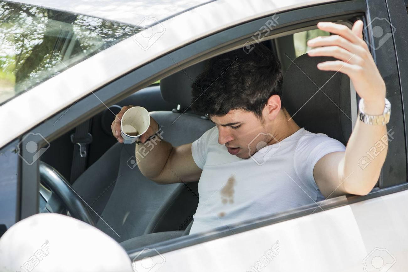 6047f89a6 Hombre joven que tiene un mal día, Conductor distraído Mirar hacia abajo en  la frustración al café derramado en la camiseta blanca mientras estaba ...