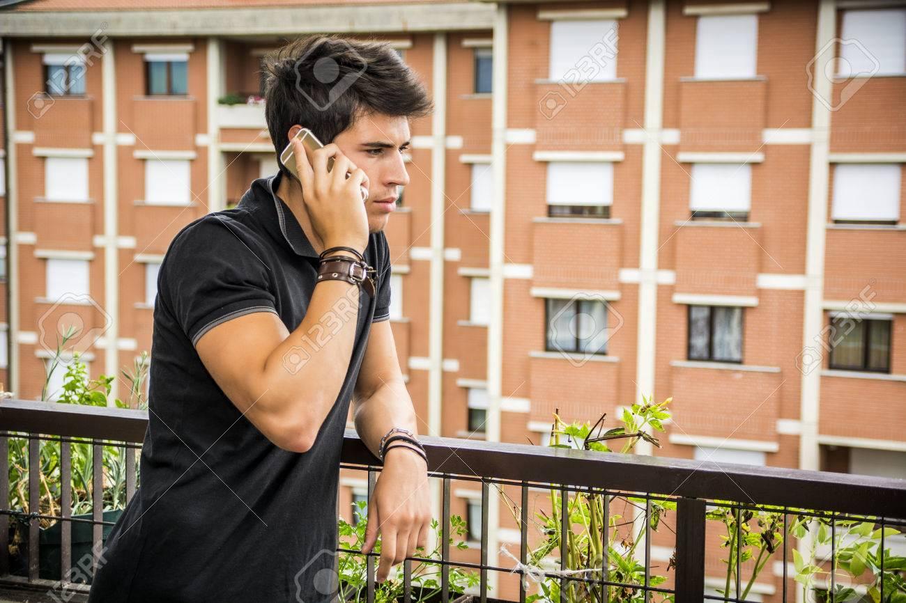 Apuesto Joven Al Aire Libre Hablando Por Teléfono Celular En La Terraza De Su Casa
