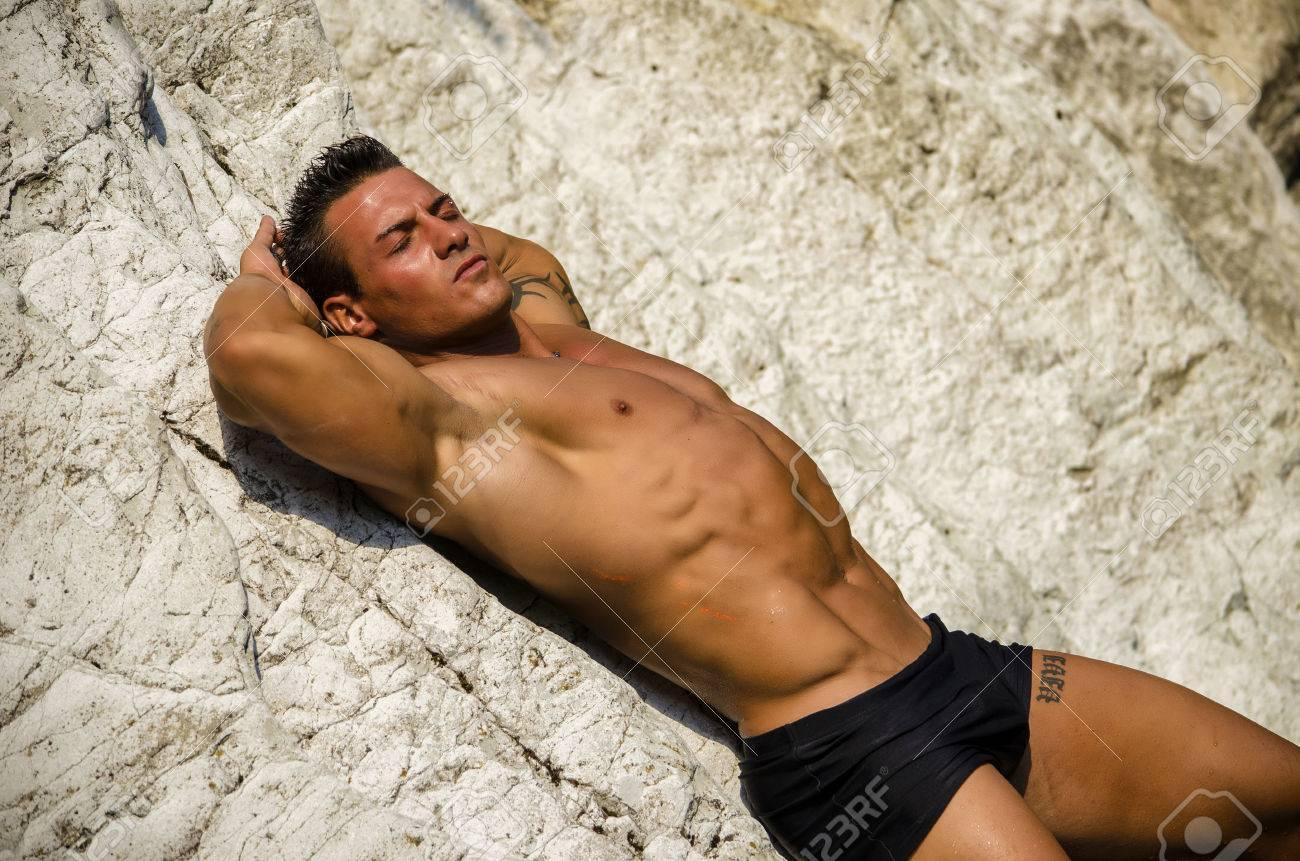 Hombre Joven Atractivo Por La Que Se Desnuda En Las Rocas Blancas Los Ojos Cerrados Vestida Sólo Con Traje De Baño Negro