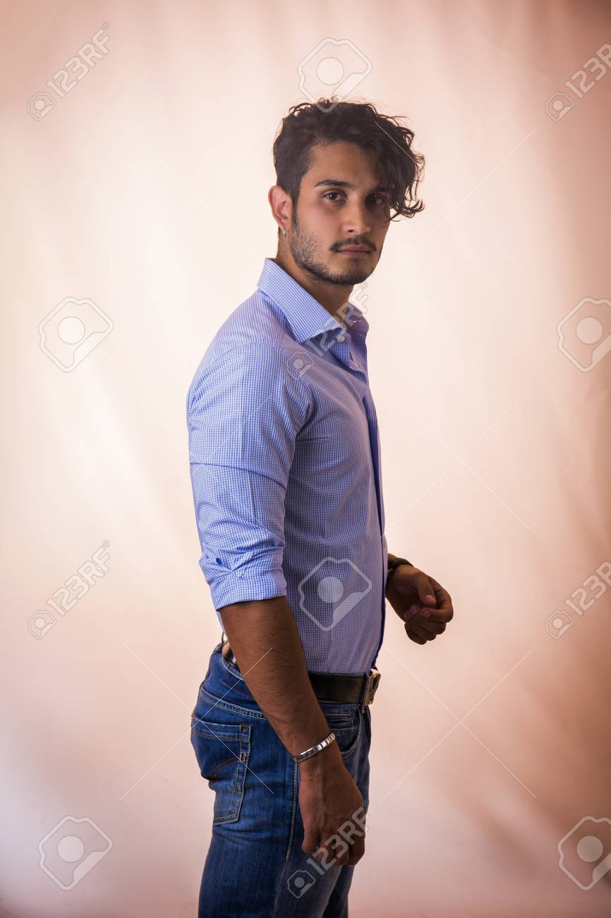 0e08c594ed3 Portrait Of Brunette Young Man In Light Blue Shirt And Jeans ...