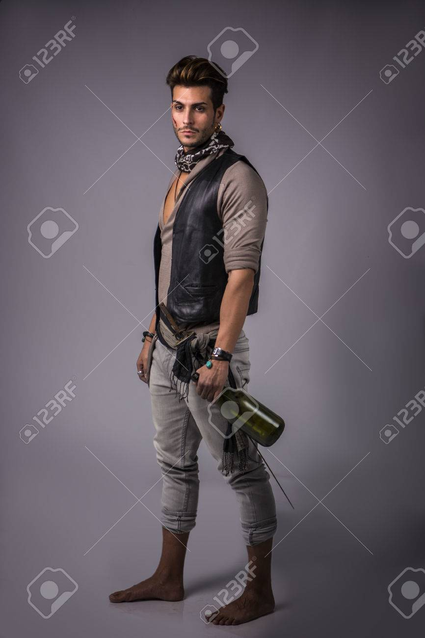 Good Looking Young Man in Pirate Fashion Outfit on Gray Background. Captured in Studio. - 73481657
