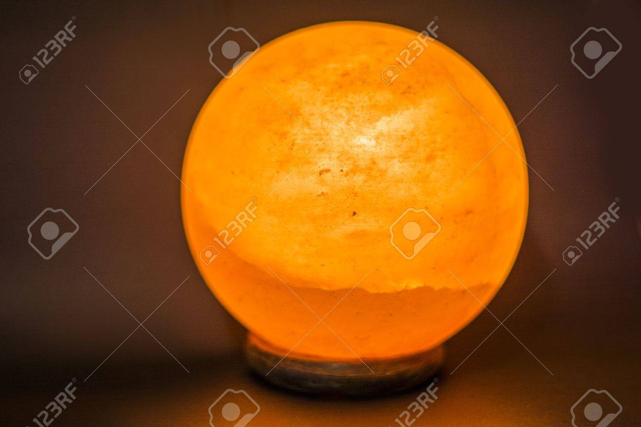 Stock Photo   The Lamp Placed Inside Of The Salt Stone. Horizontal Indoors  Shot Of Himalayan Salt Round Or Spheric Lamp