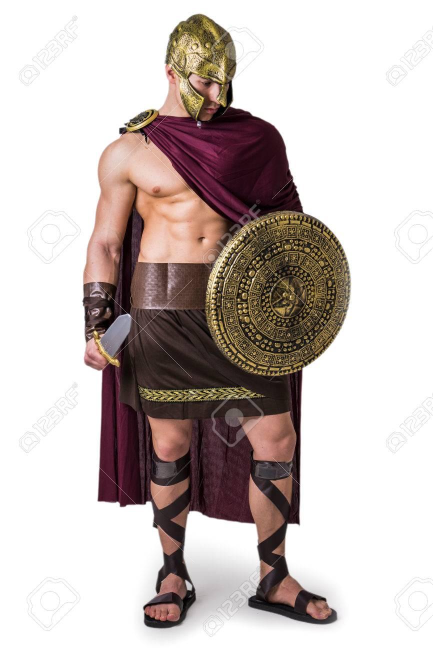 05f6132187df Banque d images - Jeune bel homme musclé posant en costume de gladiateur  romain ou spartiate avec bouclier et épée, debout isolé sur fond blanc en  studio
