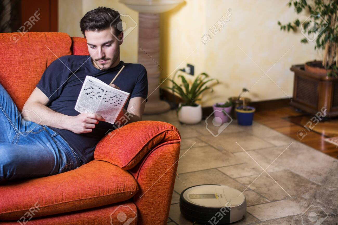 Young Man Sitting Doing A Crossword Puzzle Looking Thoughtfully Stock Photo Picture And Royalty Free Image Image 125881055