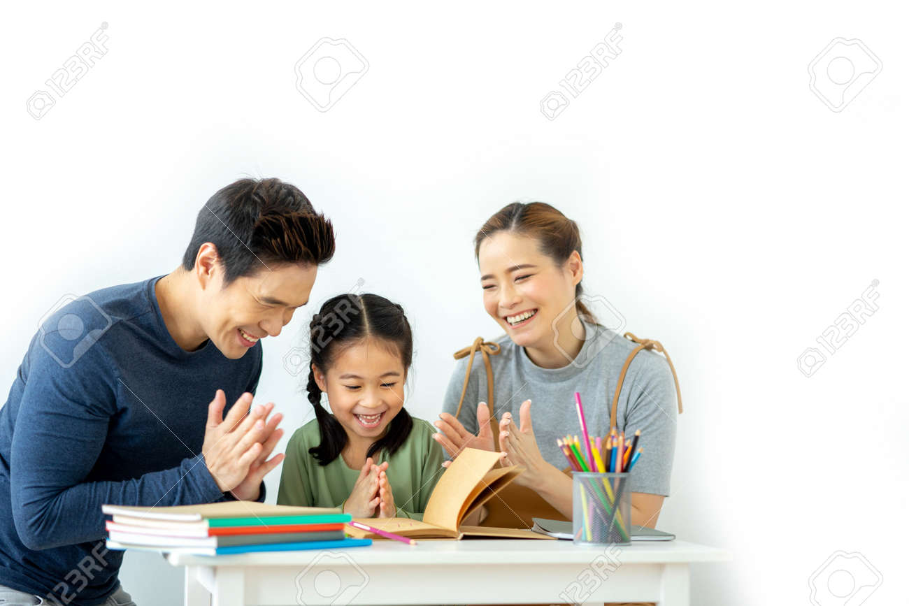 Asian young mother and father with little daughter sit at desk learning and making homework spending free time together at home. Education concept. - 158120215
