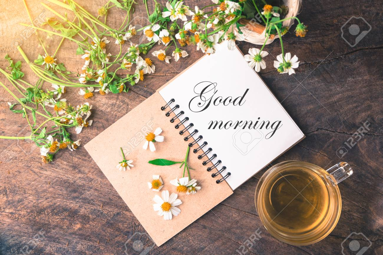 Good Morning Text On Notebook With White Flower And Bas Ket Of
