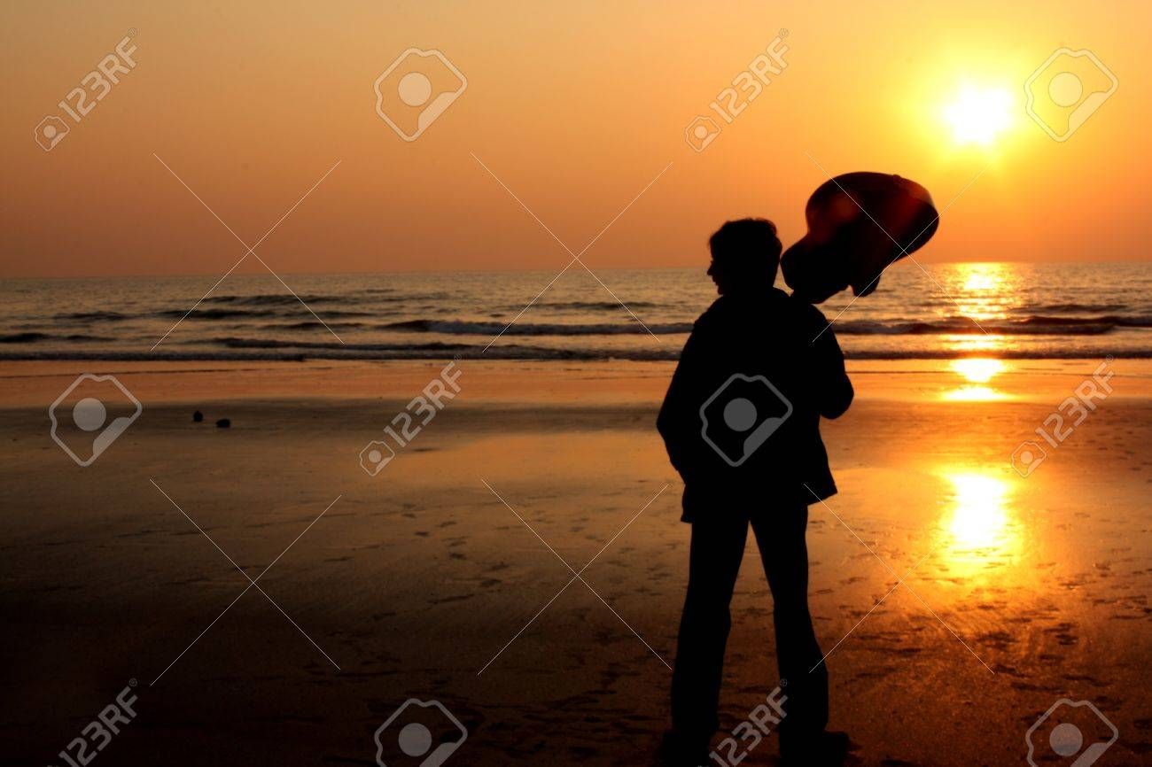 A silhouette of a lonely guitarist on a beach. Stock Photo - 11065526