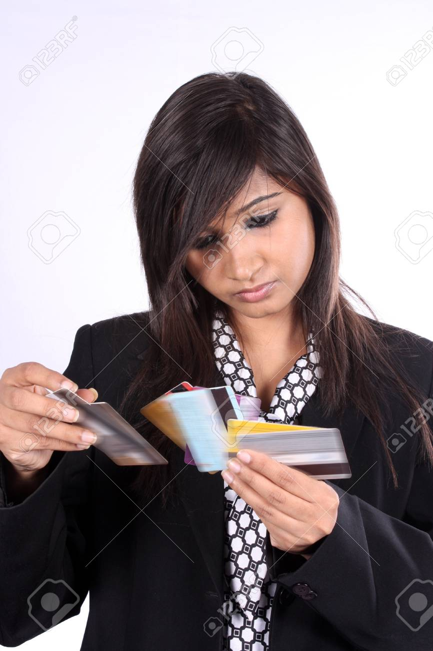 A young indian businesswoman checking different credit cards a young indian businesswoman checking different credit cards on white studio background stock photo reheart Images