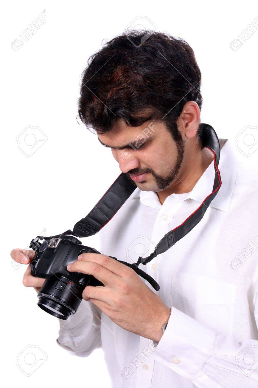 A young Indian professional photographer checking the quality of the photographs after clicking them, on white studio background. Stock Photo - 14602097