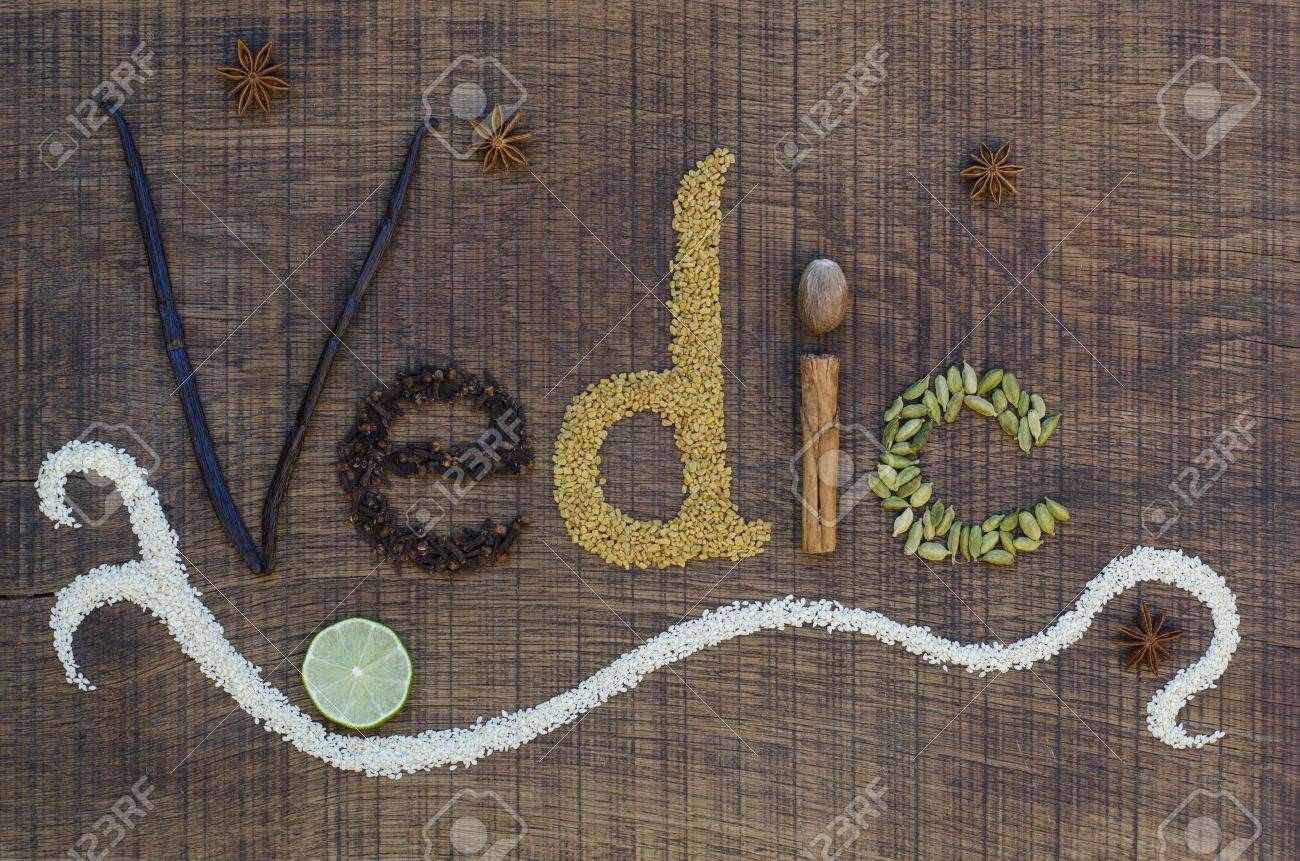 The word Vedic spelled out in a decorative way, with spices and seeds used in the ayurveda diet and healing, on a wooden countertop, surface. Stock Photo - 15071626