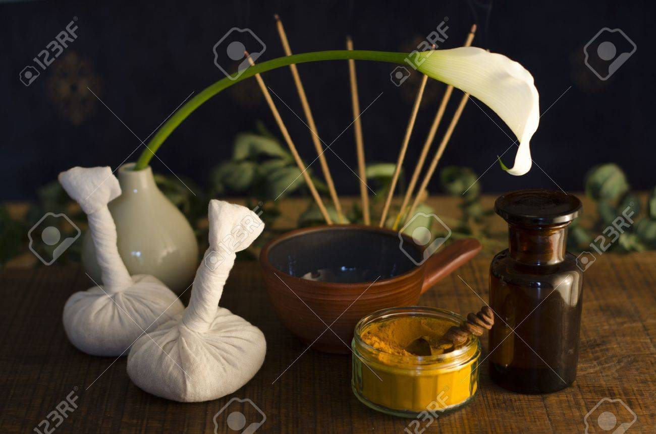 An arrangement of turmeric, spice, oil bowl and bottle, and massage poultice boluses used in Ayurveda massage, with an exotic flower and incense burning in the background. Stock Photo - 15071610