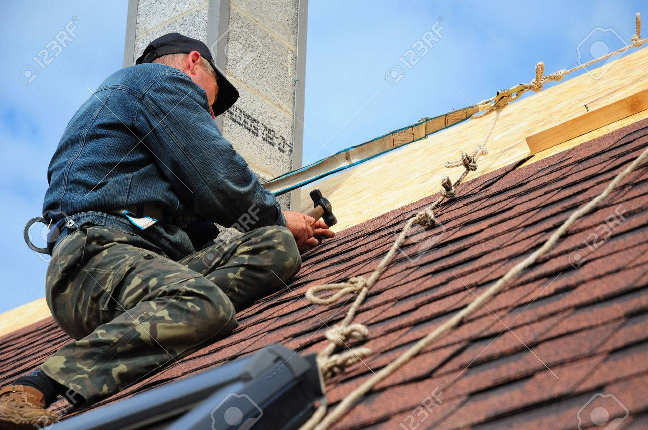 Roofing Contractor. Roofing Construction and Building New House with Modular Chimney, Skylights, Attic Exterior. Roofers Install, Repair Asphalt Shingles or Bitumen Tiles on the Rooftop Outdoor - 72086226
