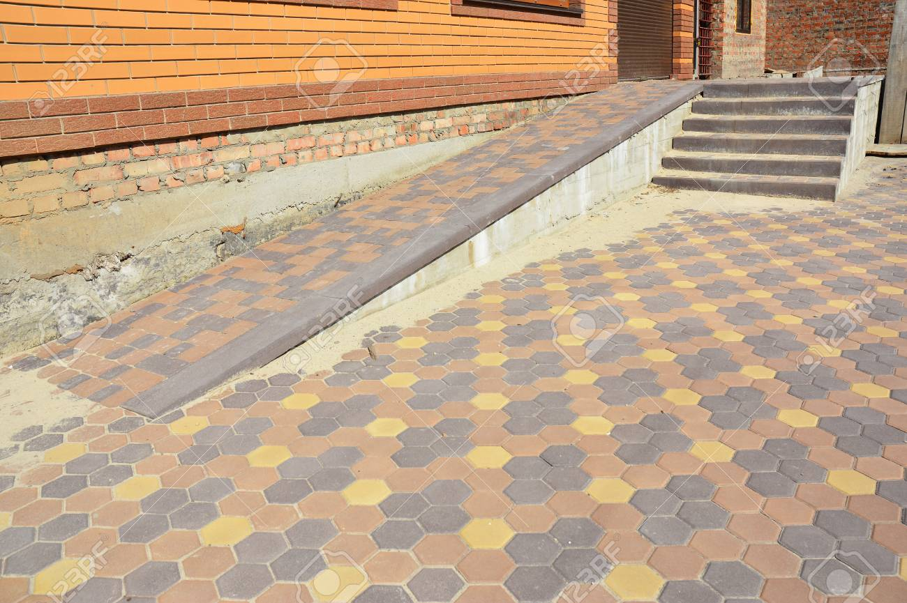 Building Ramp For Wheelchair Entry And Stairs With Colorful Pavers.  Pavement. Stock Photo