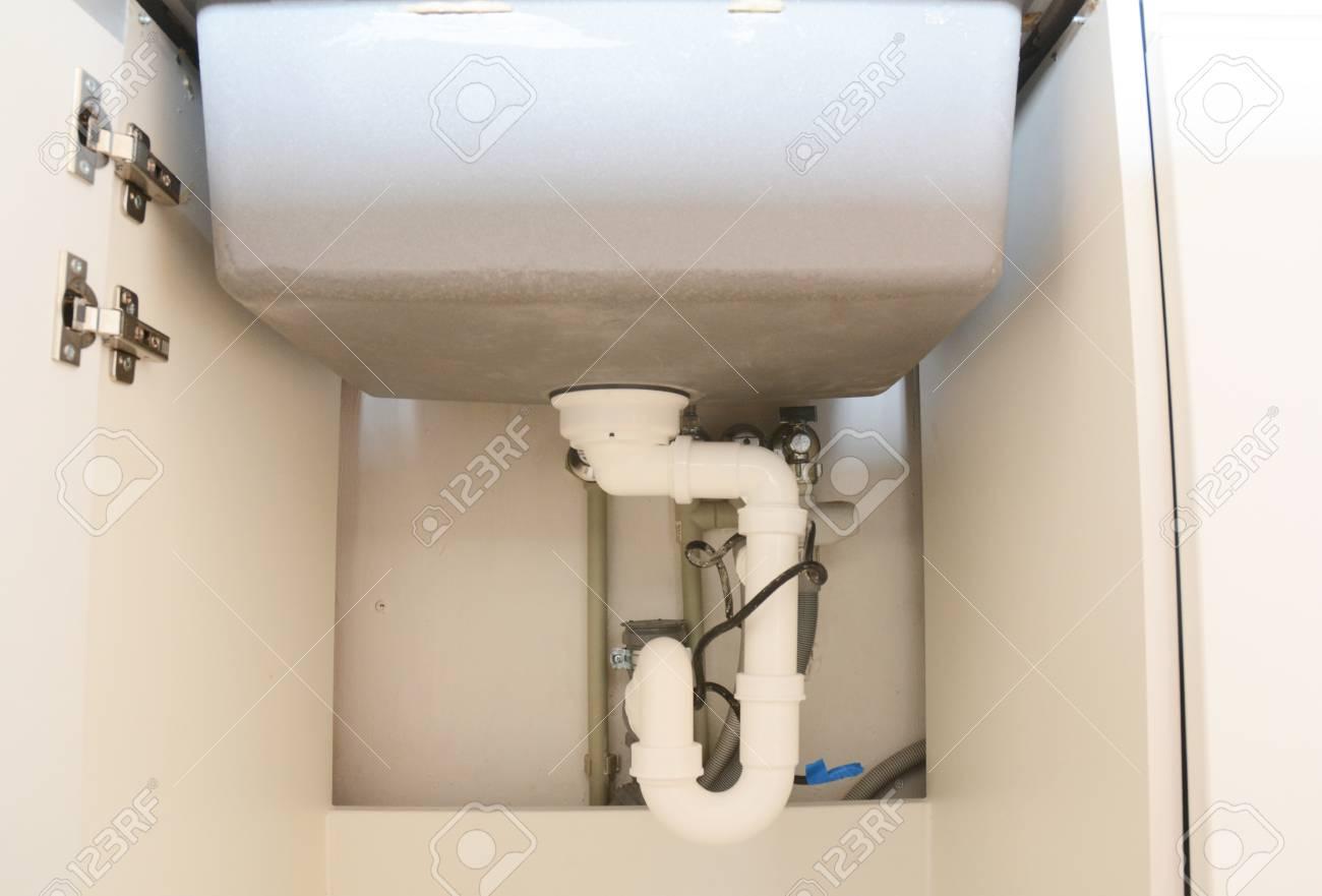 Close up on ceramic kitchen sink installation with sink drain..