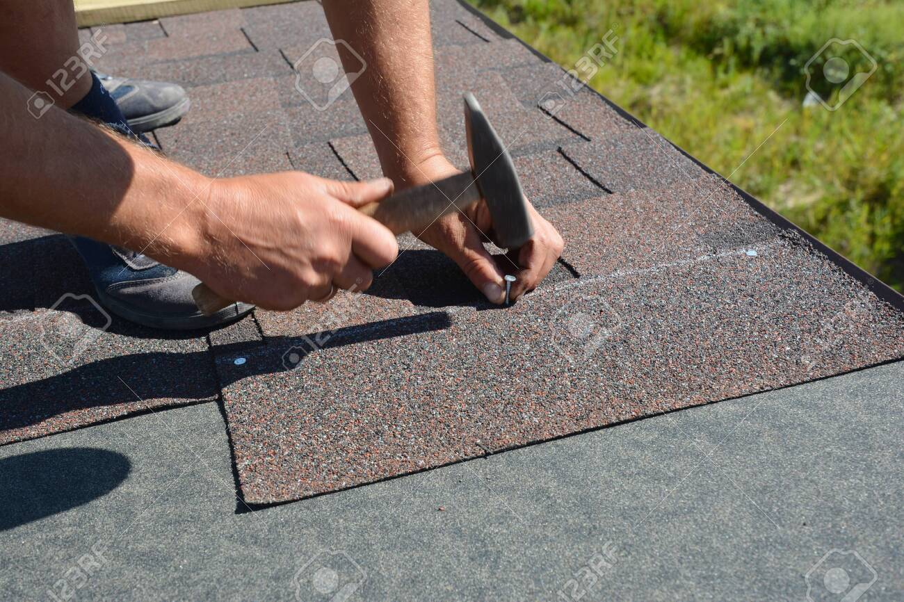 Roofer Installing Asphalt Shingles On House Construction Roof Stock Photo Picture And Royalty Free Image Image 119373829