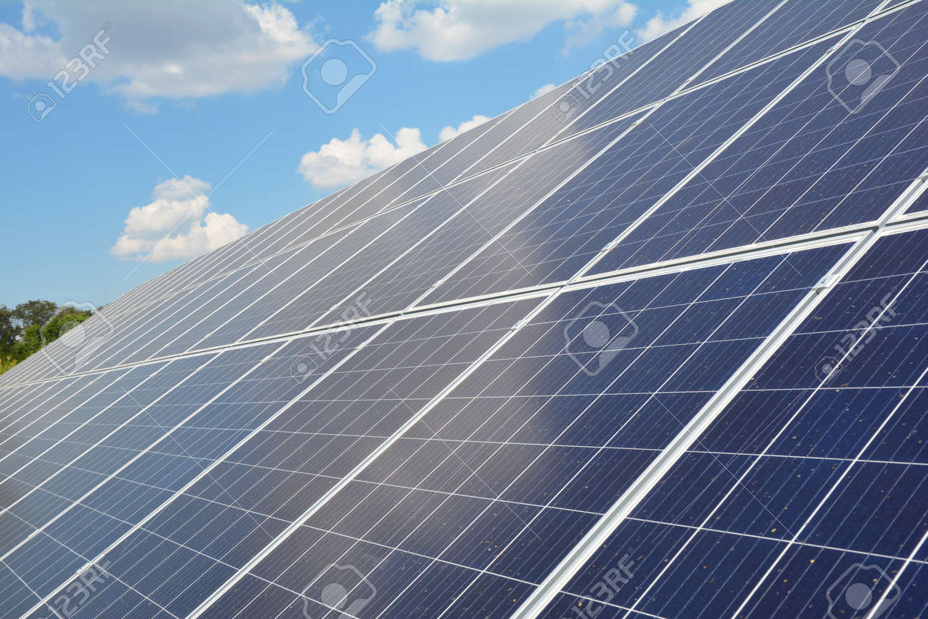 A close-up on a solar panel with numerous solar modules and photovoltaic cells against blue sky with white clouds as a source of alternative, renewable green energy. - 166013780