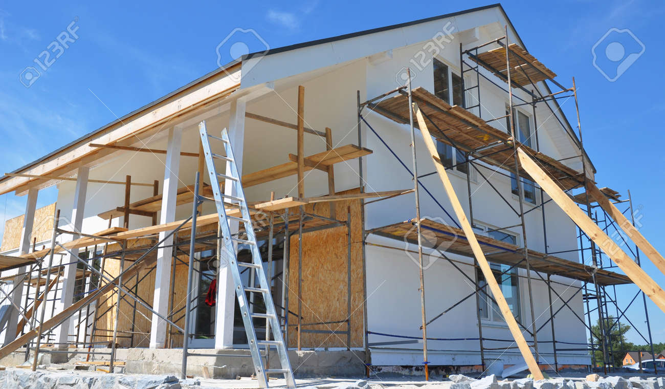 Modern house repair and renovation. Plastering, applying stucco and painting the facade walls using scaffoldings during house renovation. - 167849565
