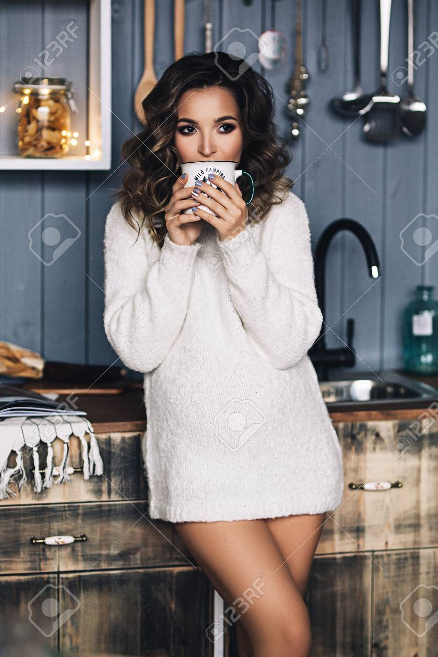 e5f1c8f1d31ba Caucasian pregnant woman with make up and curly hair in warm white sweater holds  her belly
