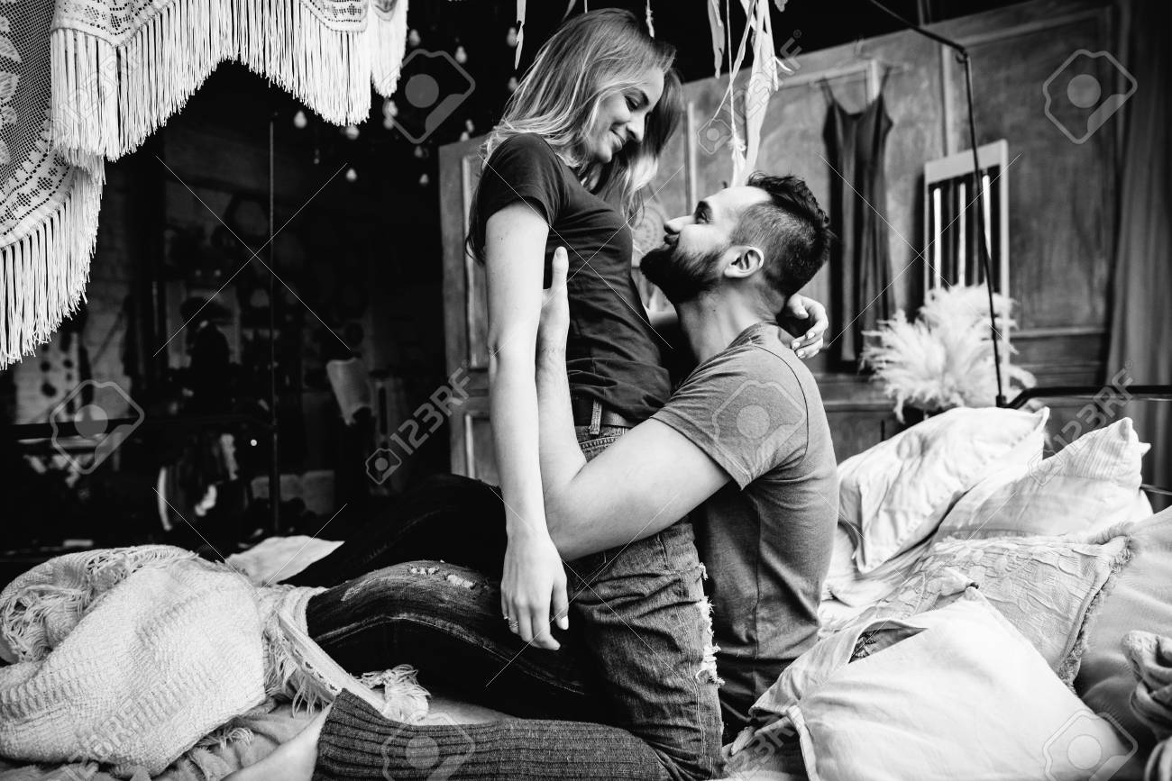 Black and white photo loving couple hug each other on the bed in big bedroom love story