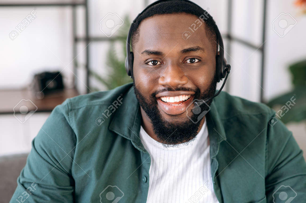 Close-up portrait of an attractive confident bearded African American operator of call center or business leader. Black businessman in headset and casual shirt looks at the camera and friendly smiling - 165342283
