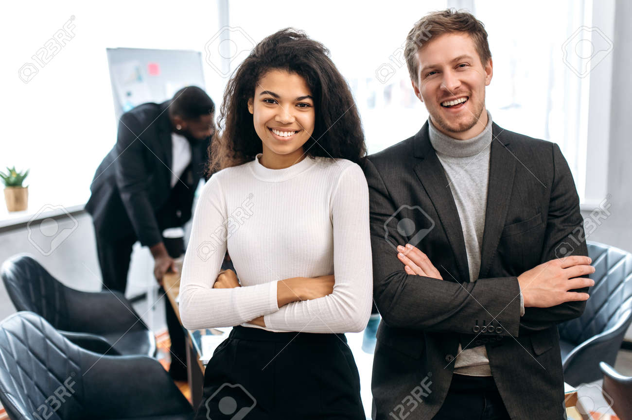 Portrait of young adult business partners are standing with cross hands in modern office,. Happy confident multiethnic colleagues in formal wear looking at the camera, smiling, teamwork concept - 165692742
