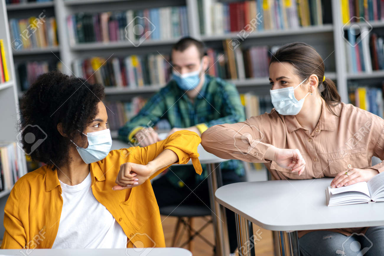 Two female student friends wearing protective face masks greeting each other bumping elbows while sitting at university library, healthcare concept, precautions, new normal - 168023130