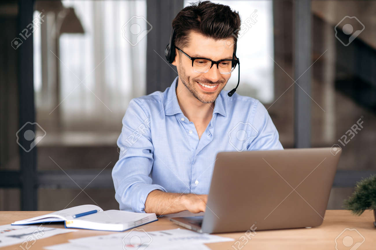 Happy confident caucasian man wearing glasses and headset, manager, freelancer or consultant, sitting in office, using laptop, chatting with client via video conference, typing on keyboard, smiling - 169833555