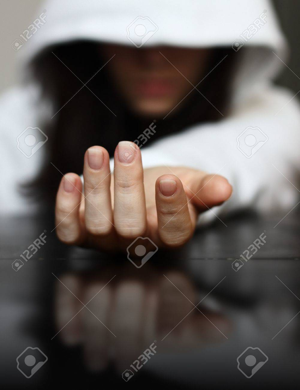 Young girl wearing hoodie sits with stretched out hand needing help Stock Photo - 15070359