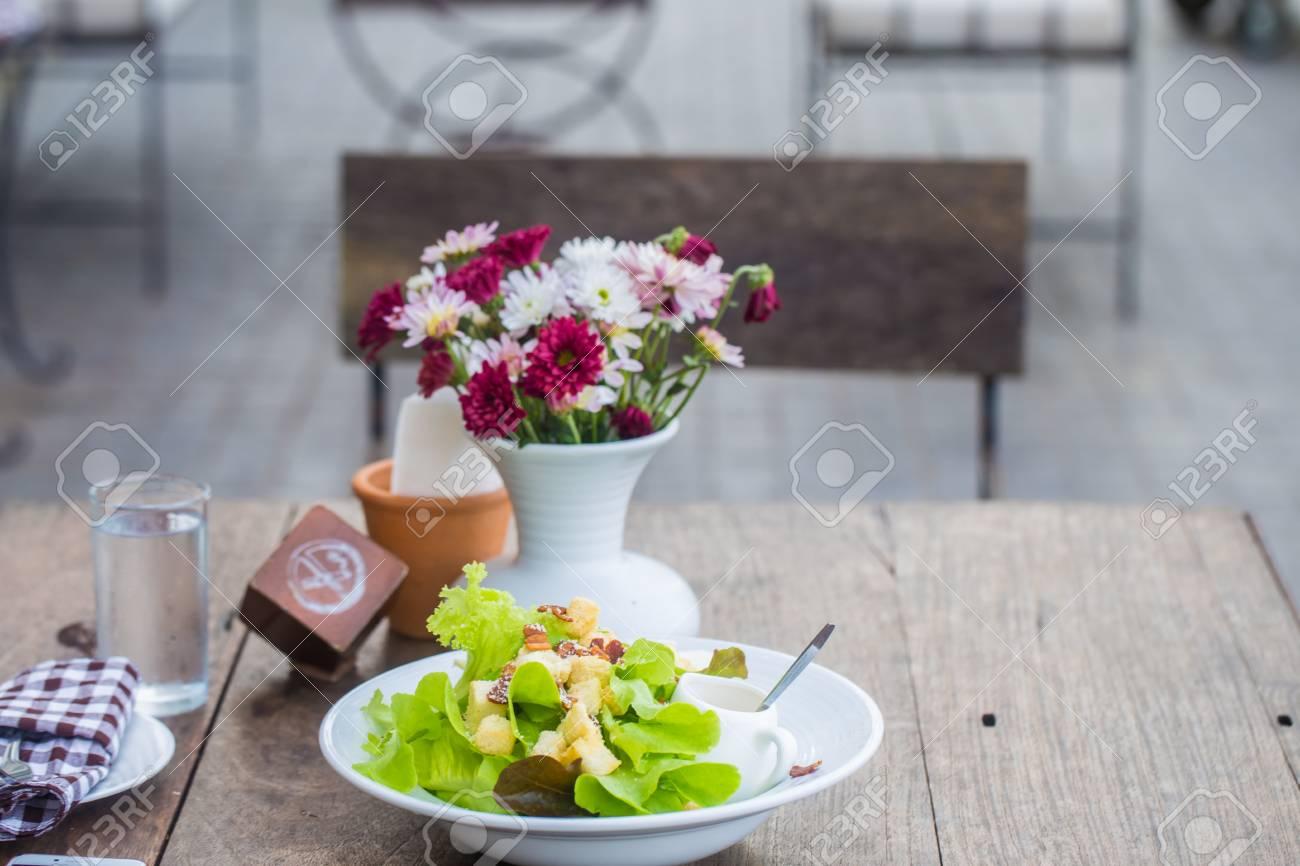 123RF.com & Homemade salad healthy food with flower vase on wood table
