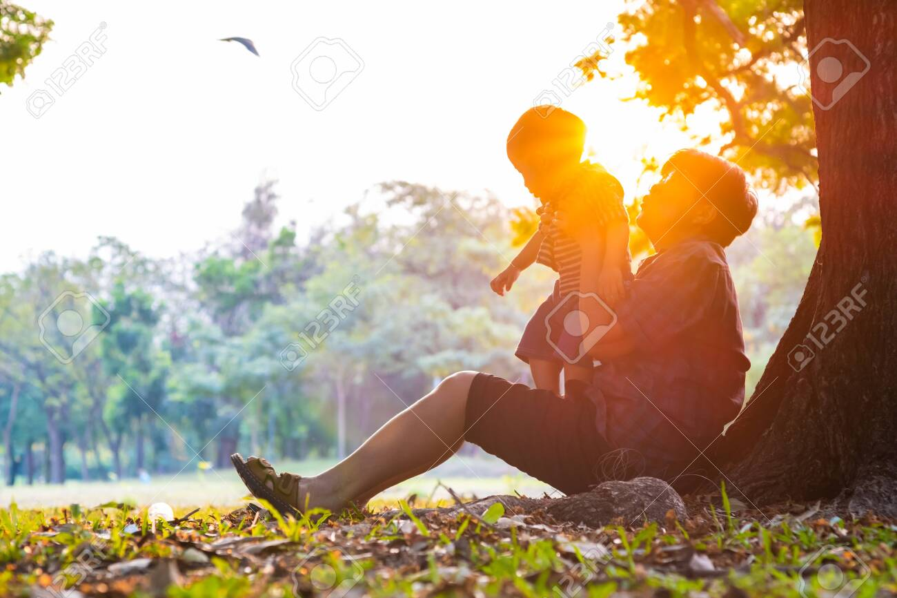 Senior elderly Grandmother Playing with grandson baby boy under tree in city park sunset light power of elationship concept - 145532199