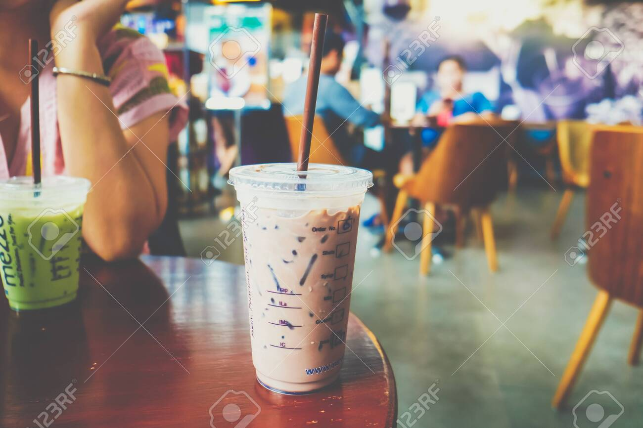 Ice coffee cup on wooden table in modern cafe blurred people background - 145949954